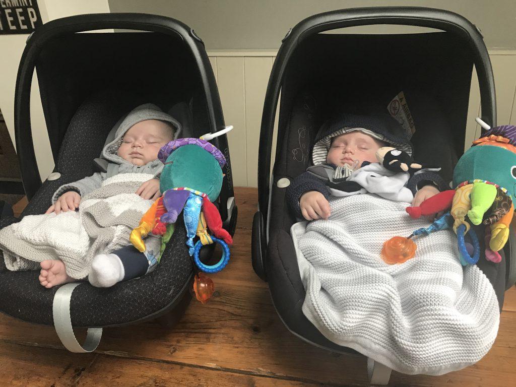 Newborn twins in car seats on a kitchen table asleep