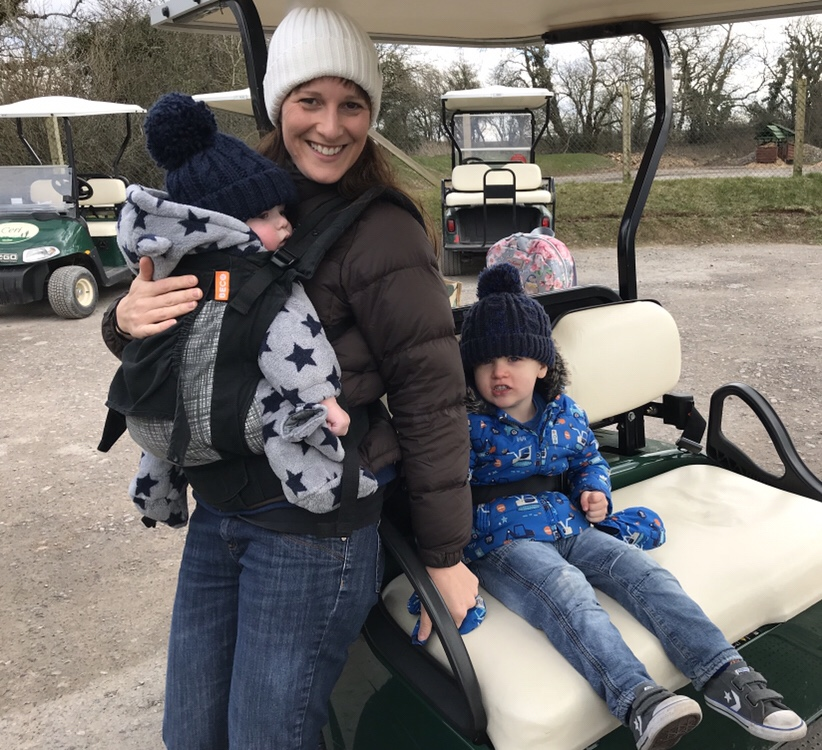 Family with baby and toddler on a golf buggy