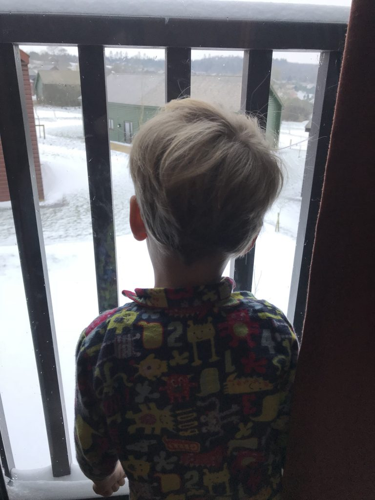 Toddler looking out the window at snow at Bluestone