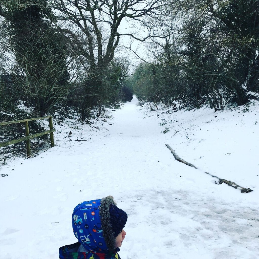 Toddler playing in the snow at Bluestone