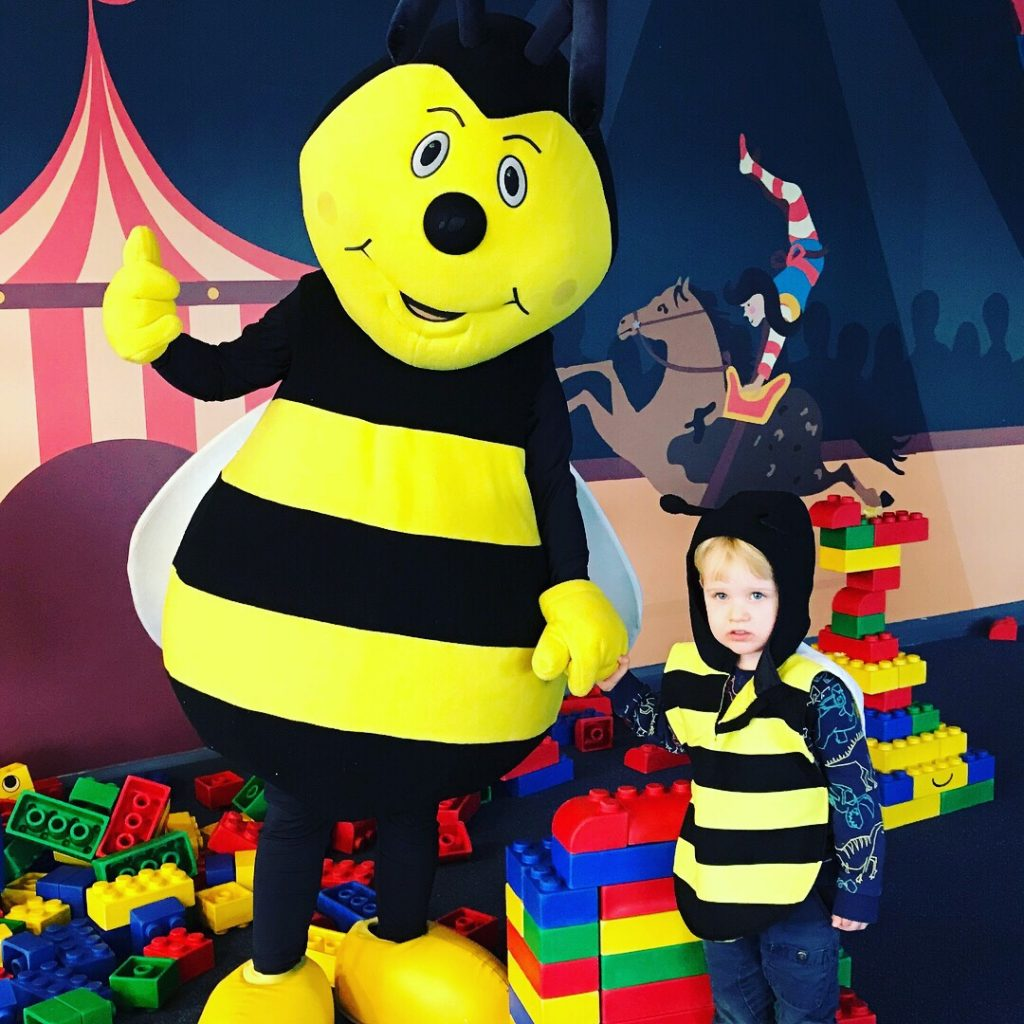 A toddler and bumble bee mascot at Bluestone