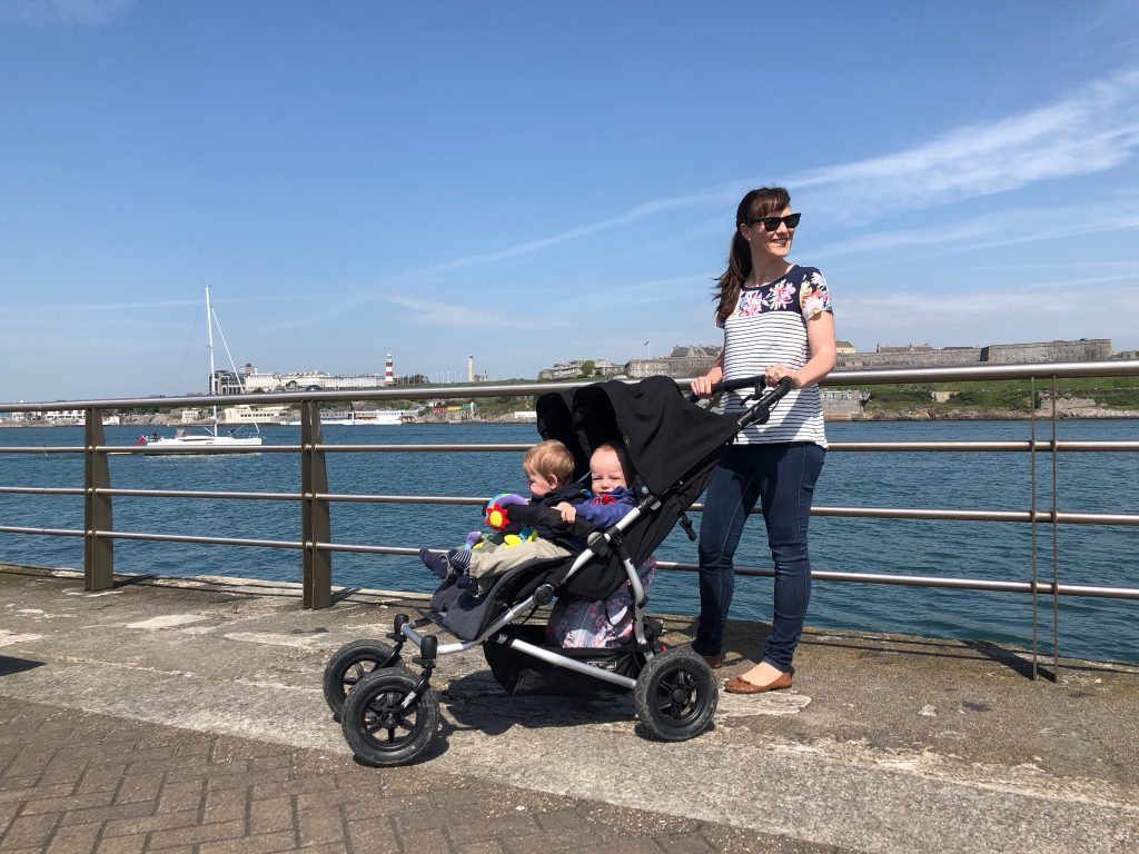 Mum pushing buggy at Mount Batten one of the best outdoor spaces in Plymouth