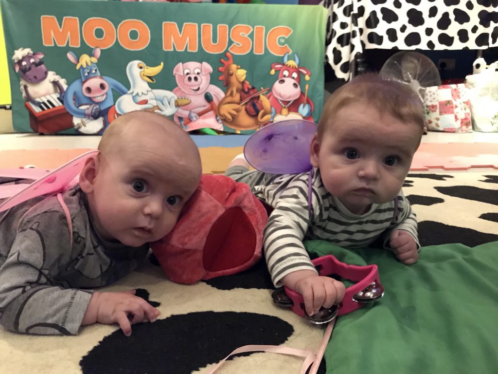Twins lying on their fronts at a Moo music baby group