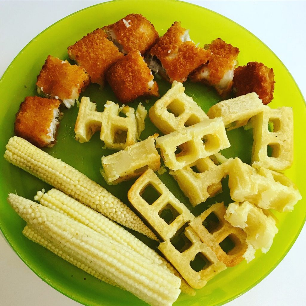 Green plastic plate of food with chopped up potato waffle and fish finger