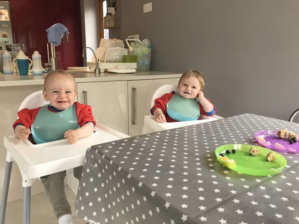 Grey Messy Me oil cloth table cloth on a table with twin babies in a mess with food at their high chairs