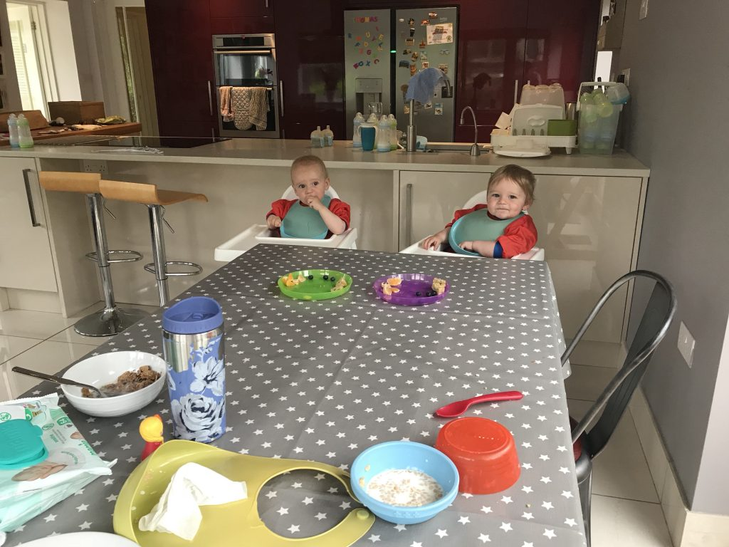 Baby boy twins at a table in their high chairs with lots of plates and bowls on a grey oil cloth table cloth
