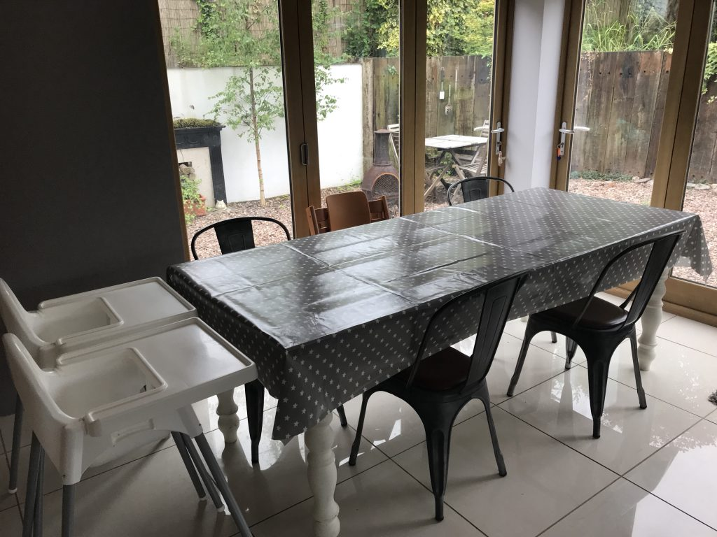 A large table and chairs covered with a grey and white oil cloth Messy Me table cloth