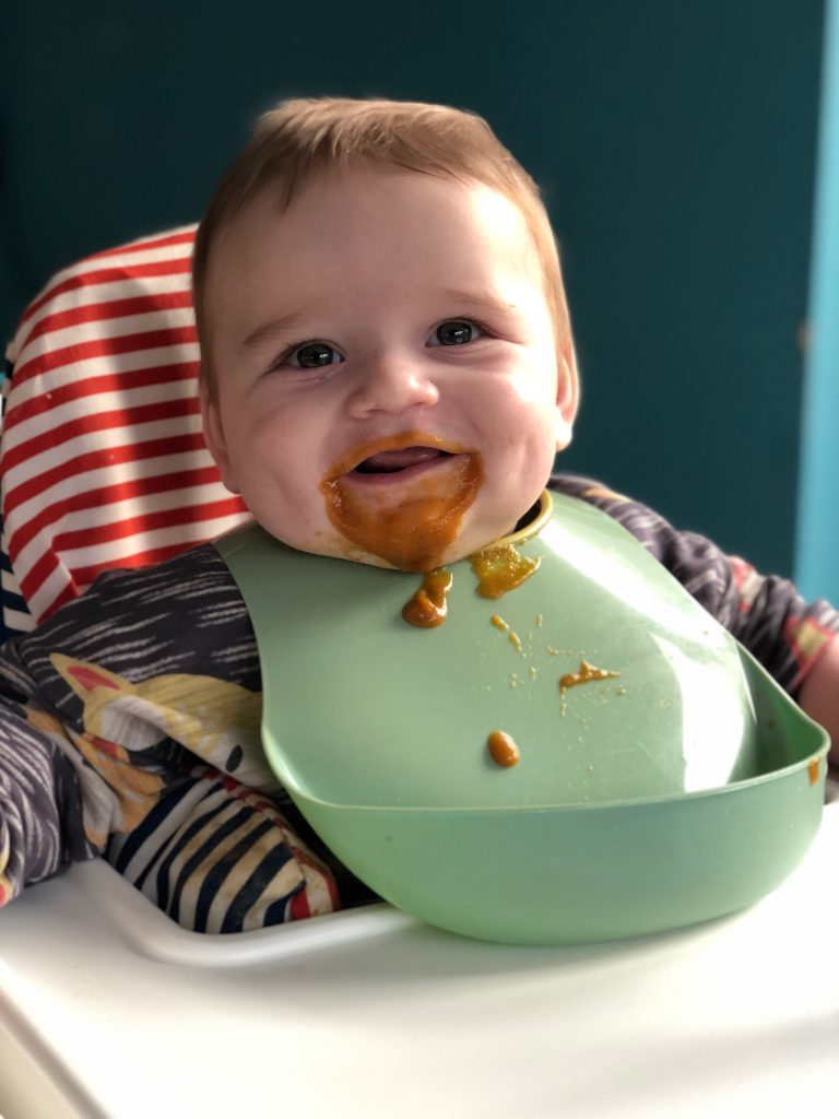 Baby boy with food all over his face and down his bib smiling