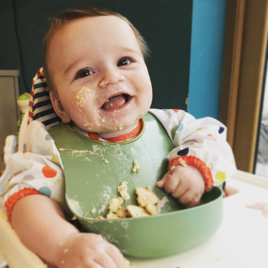6 month old baby boy wearing a bib and sitting in a high chair with food all over his face but smiling hugely
