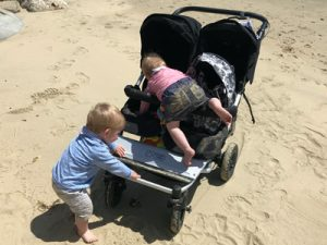 Twin toddlers climbing on their buggy on a beach