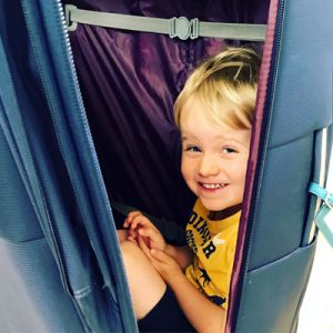 Toddler hiding in the suitcase before holiday