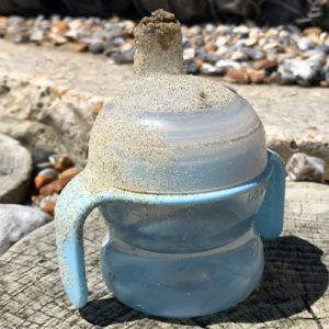 A sippy cup covered in sand