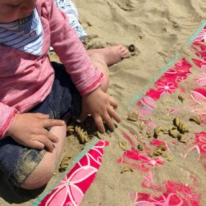 Toddler dropping pasta in the sand on a beach