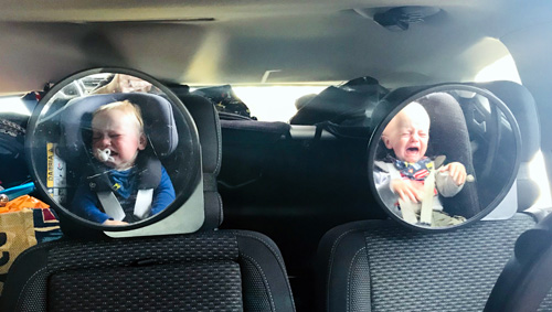 Twins crying in the back of a car on holiday