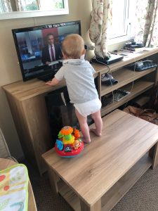 Toddler climbing on a coffee table in a caravan