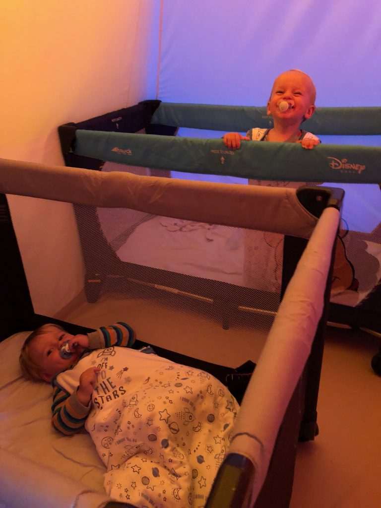 Toddlers in travel cots in a tent