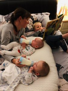 Mum bottle feeds twins at the same time as reading to her toddler
