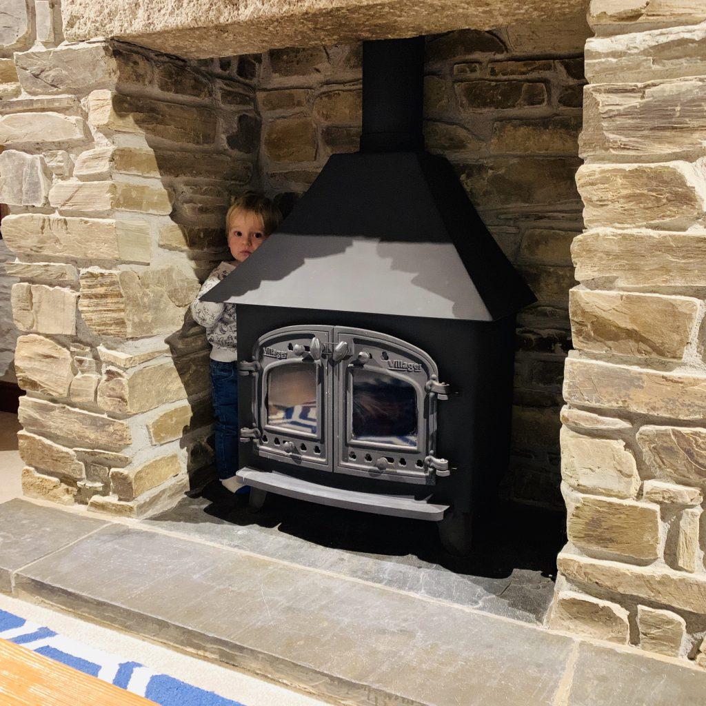 Twins hide behind a woodburner