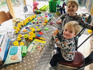 Daddy does play doh with toddlers on a weekend home alone