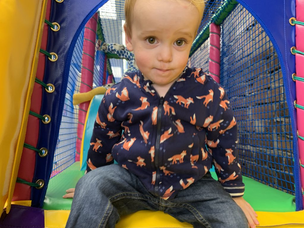 Toddler at the top of a soft play slide