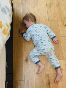 Twin One lying on wooden floor with stomach bug for the bloggers linky