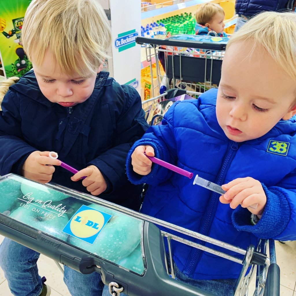 Children in a shopping trolley playing with calpol syringes