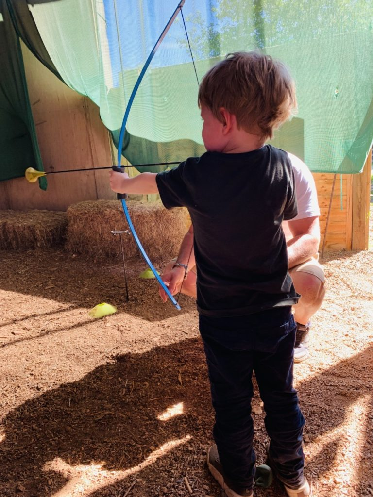 Thomas trying out mini archery at Sandy Balls