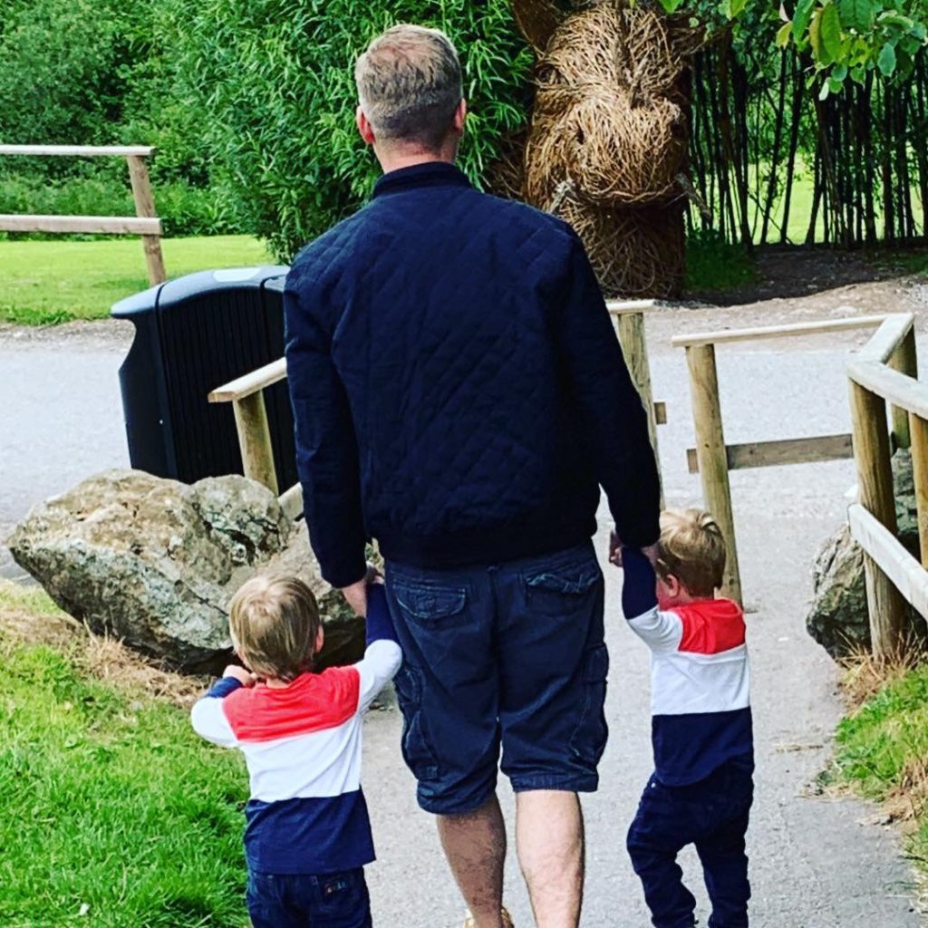 Daddy holding the twins hands as they walk