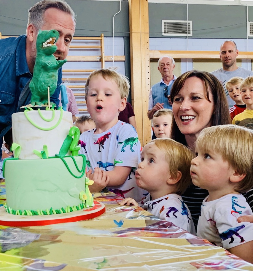 Four year old and two year old twins blow out the candles on their dinosaur cake at a kids' birthday party
