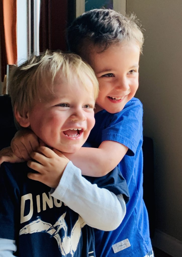 Four year old and two year old friends have a cuddle on holiday at Bluestone
