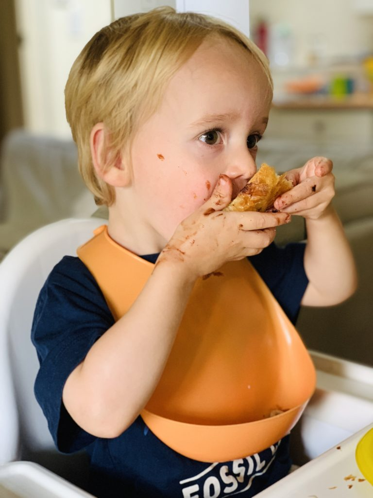 Toddler enjoying a pain au chocolat