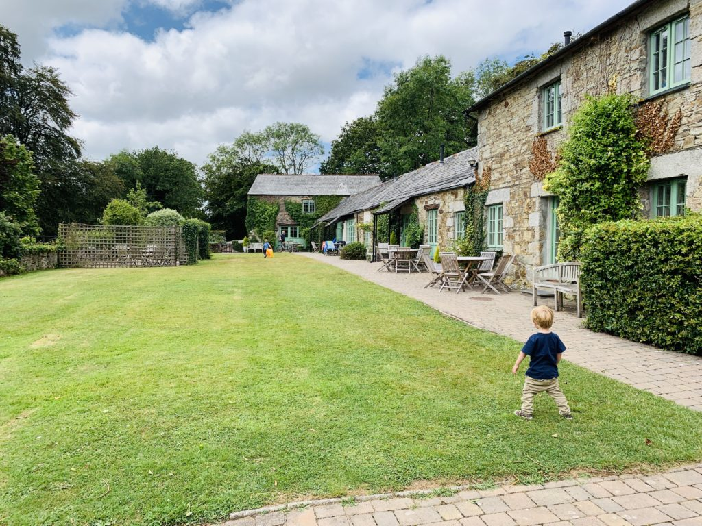 Toddler on the lawn of Glynn Barton cottages