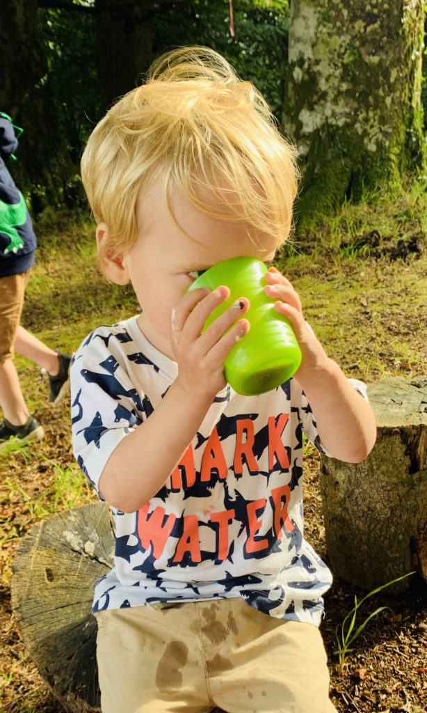Toddler drinks hot chocolate at a camp fire