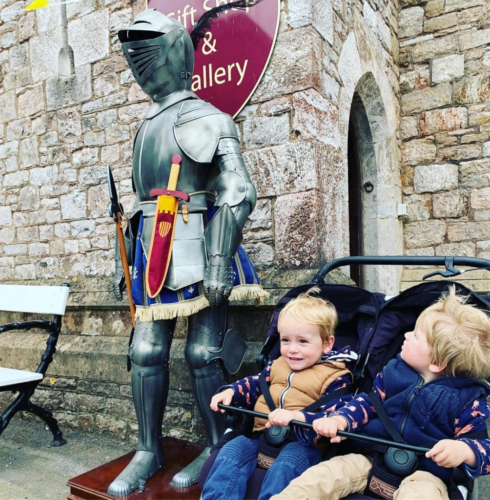 Twins looking at a knight's armour