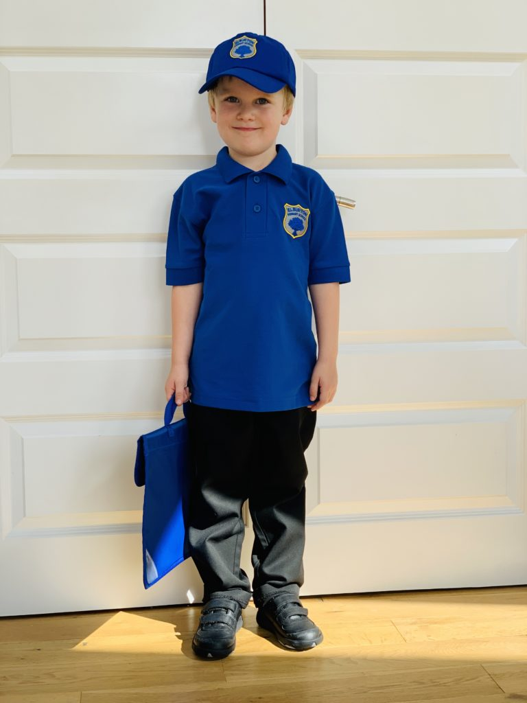 A four year old boy holding a book bag in school uniform