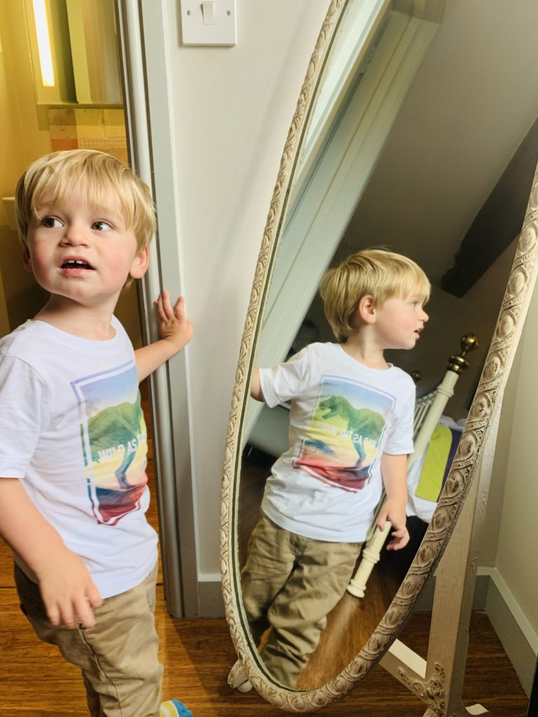 Toddler looking in the mirror at Greenwood Grange
