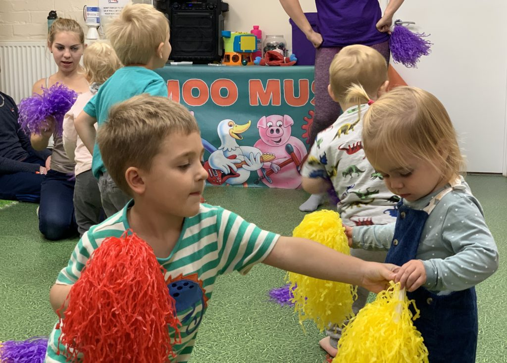Children play with pom poms at moo music