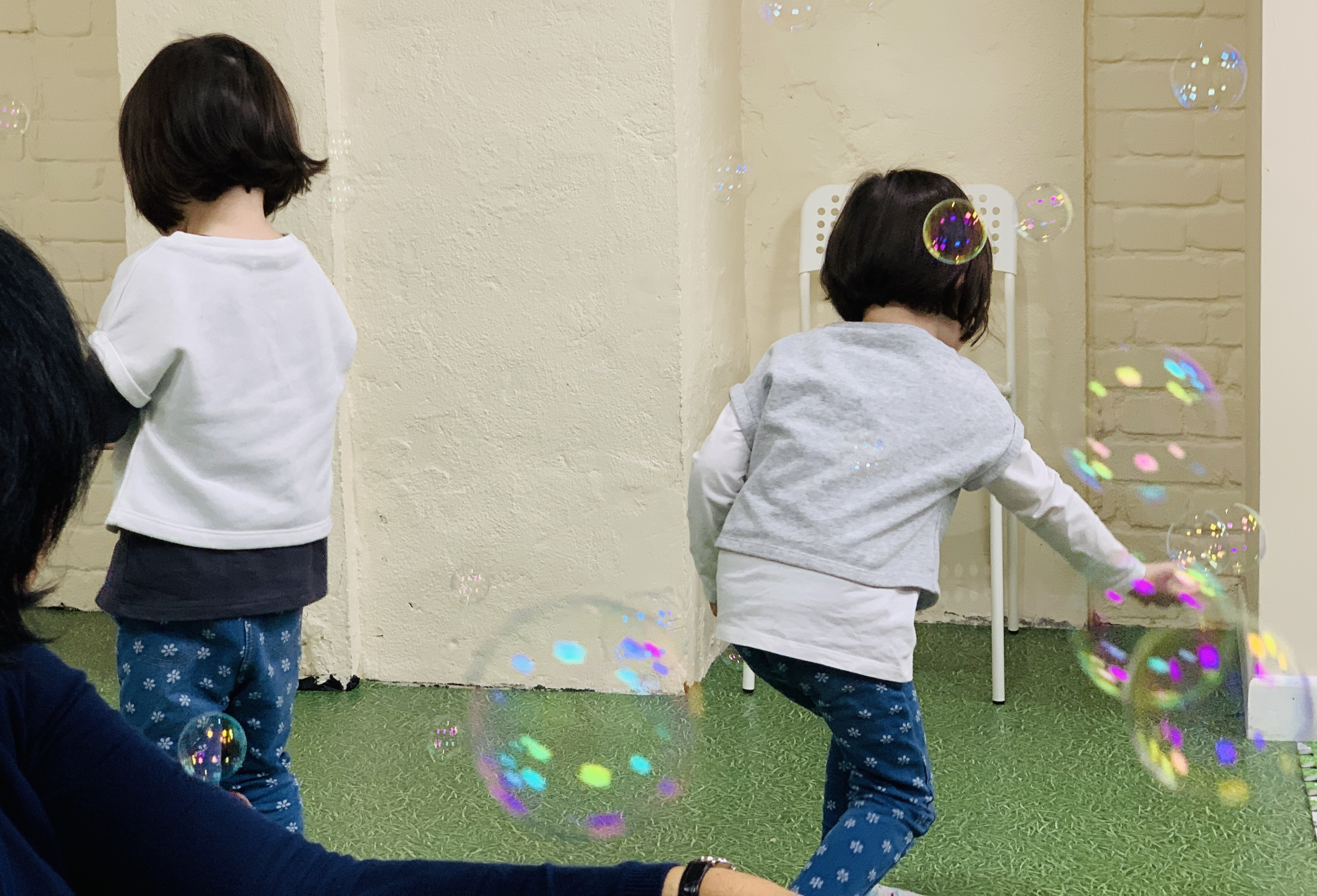 Twin girls enjoy bubble popping at moo music