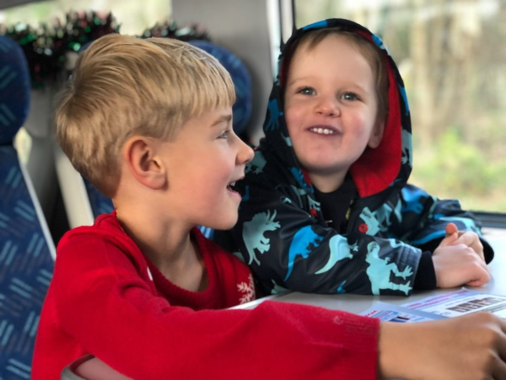 Boys enjoy a trip on a santa train at christmas