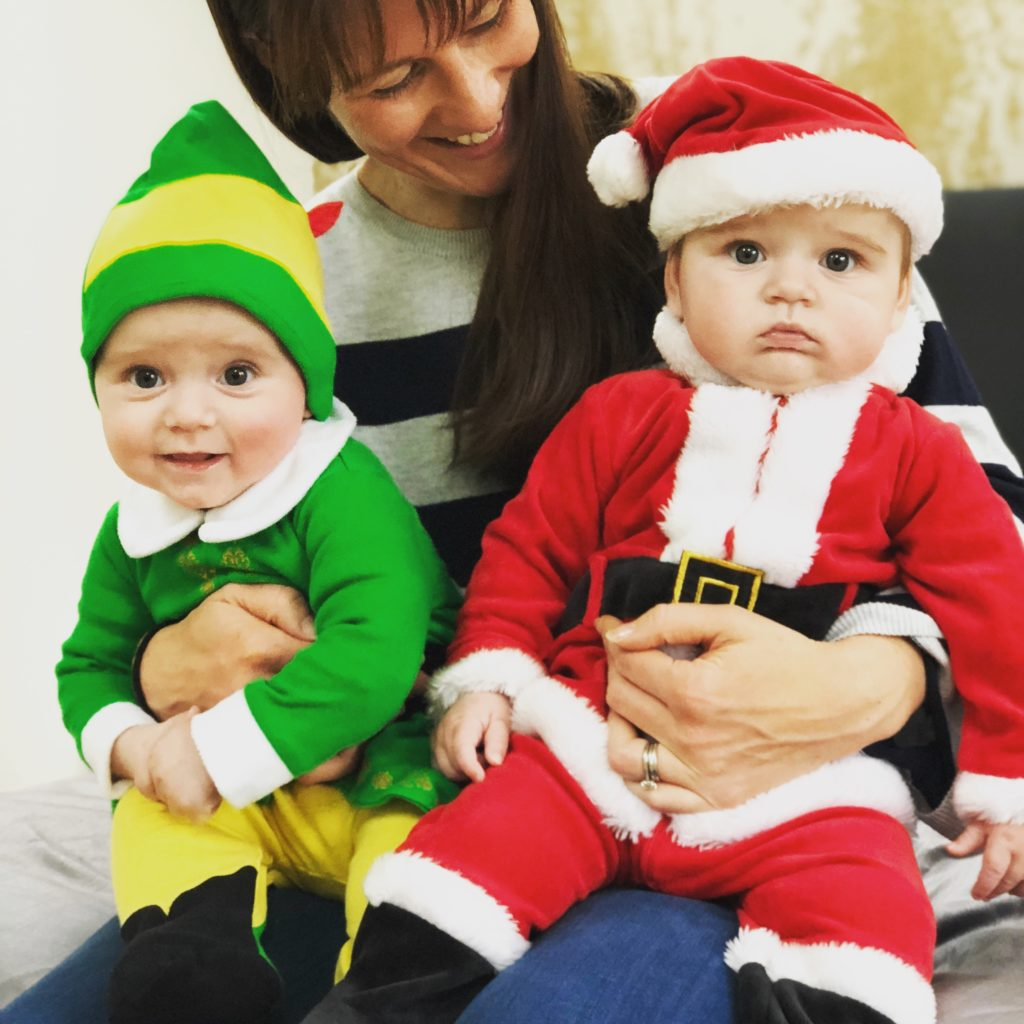 Babies dressed as Father Christmas and an Elf