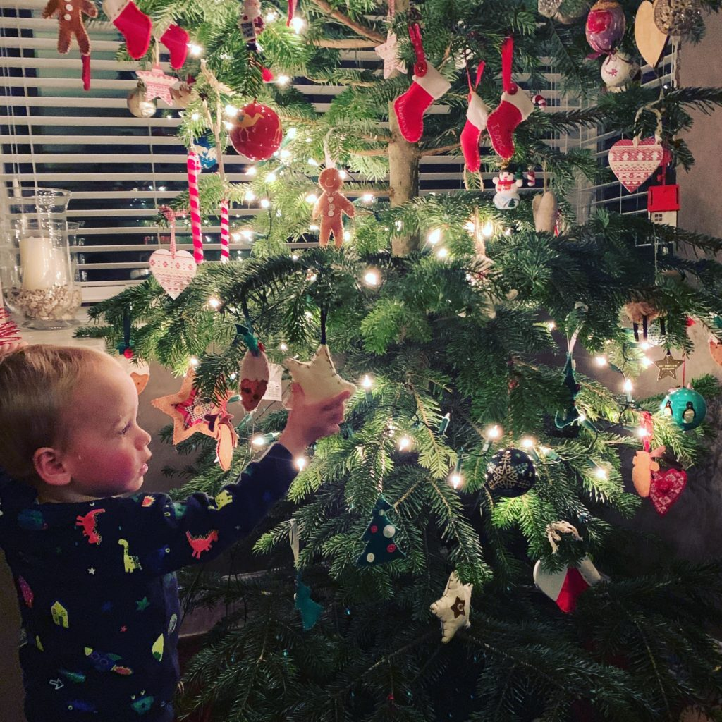 toddler next to Christmas tree