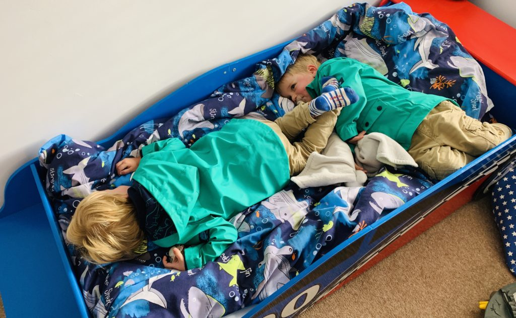 Twins ready for the school run but collapsed on big brother's bed