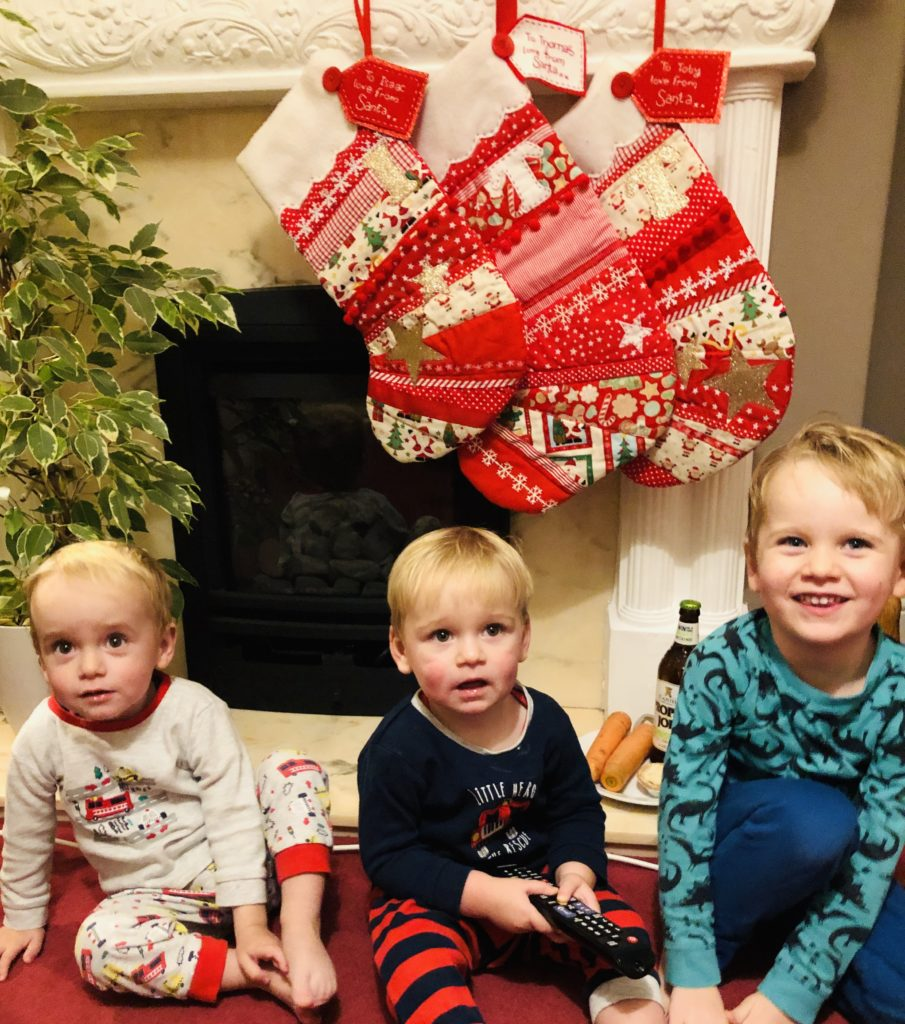 Three boys in front of the Christmas mantelpiece photo as a Christmas tradition