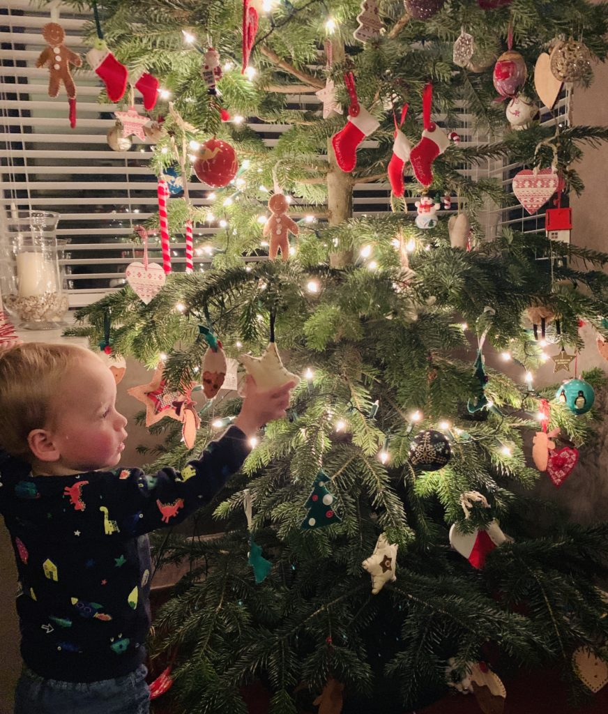 Toddler taking decorations off the Christmas tree