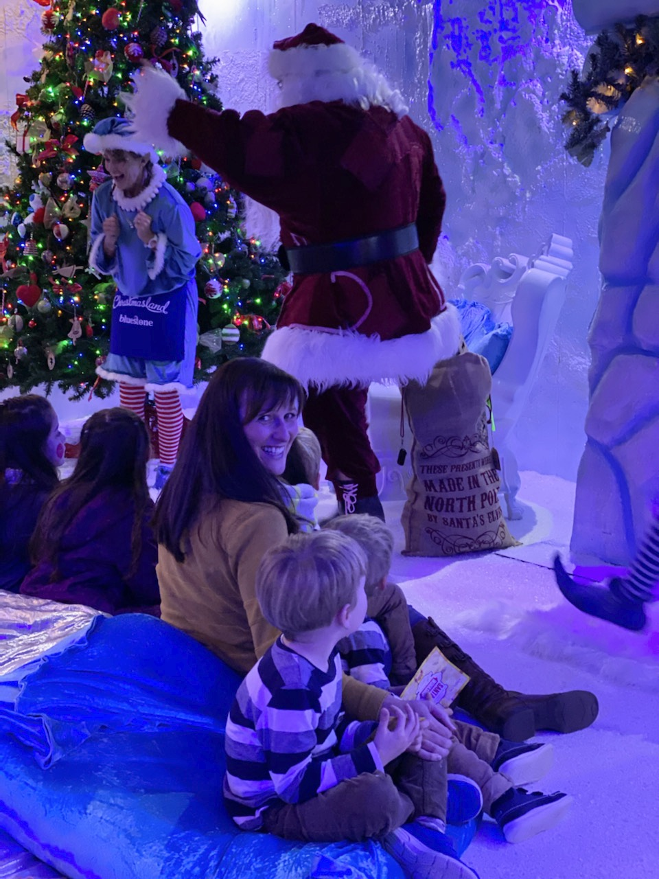 Family watch Santa arrive in his workshop at Bluestone's Christmasland