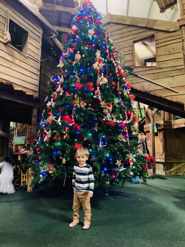 Toddler with a Christmas tree at Christmasland, Bluestone