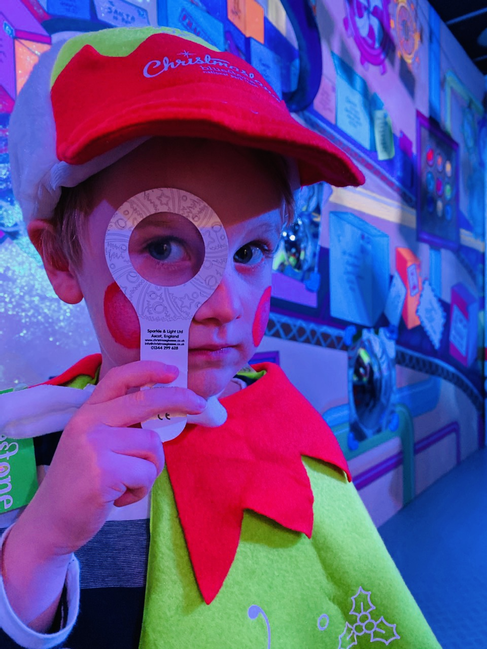 Little boy dressed as an elf with a magnifying glass at Christmasland
