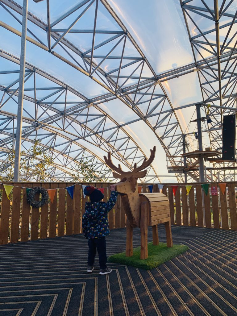 Toddler says hello to a wooden reindeer at Bluestone's Serendome