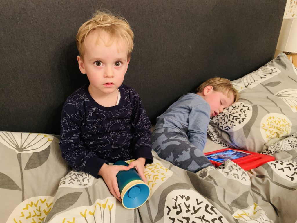 Toddlers on a bed, one asleep before bedtime