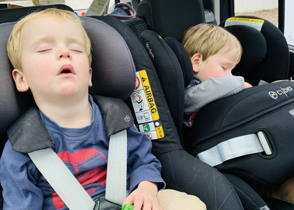 Twins sleeping in the car after the baby milestone of giving up the nap